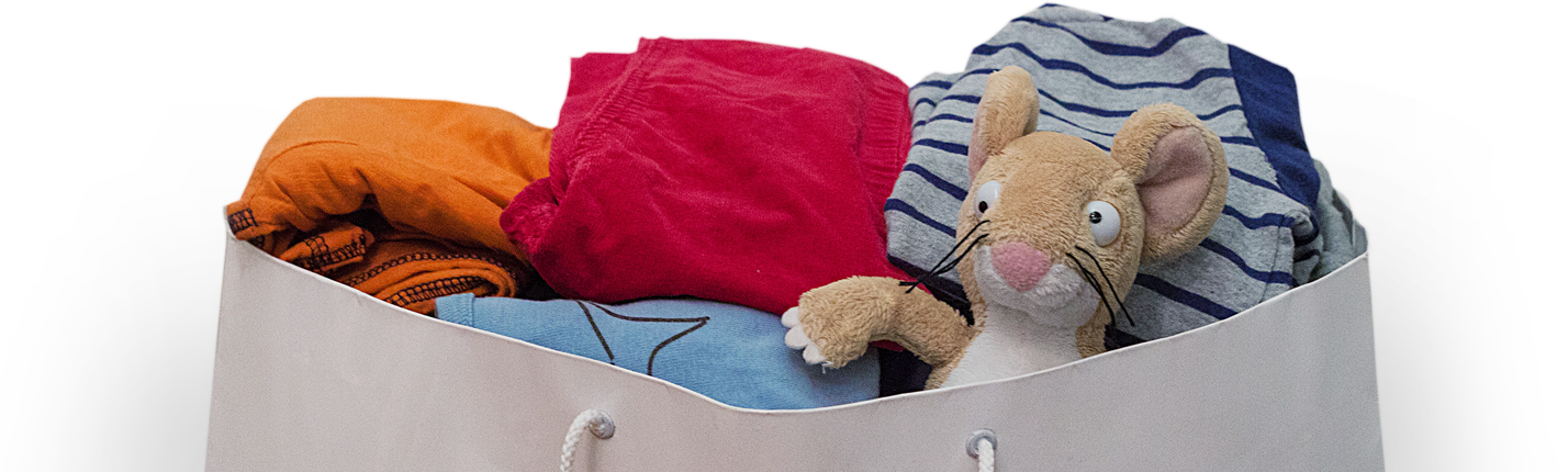A bundle of clothes spilling from a bag with a cuddly mouse looking out over the edge.